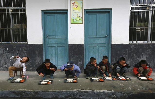 Students have lunch outdoors at a primary school in Tongguan village, Liping county, Guizhou province, November 24, 2014. According to the headmaster, there is a school dining room but students prefer eating outside as the room is dimly lit. (Photo by Reuters/Stringer)
