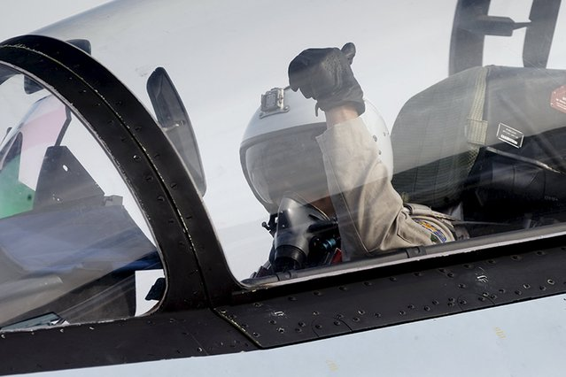 A pilot of a Sukhoi Su-30 fighter jet gestures before taking off at the Hmeymim air base near Latakia, Syria, in this handout photograph released by Russia's Defence Ministry October 22, 2015. (Photo by Reuters/Ministry of Defence of the Russian Federation)