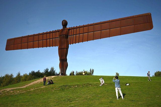 """Visitors are seen at the iconic sculpture designed by Antony Gormley """"Angel of the North"""" in Gateshead, northeast England, on September 17, 2020. The British government on Thursday announced new restrictions for northeast England, the latest region to see a surge in coronavirus cases as Prime Minister Boris Johnson warned of a """"second hump"""" in nationwide transmission. Residents in the northeast, which includes the cities of Newcastle and Sunderland, will no longer be allowed to socialise outside their own homes or support bubble from Friday onwards. (Photo by Oli Scarff/AFP Photo)"""