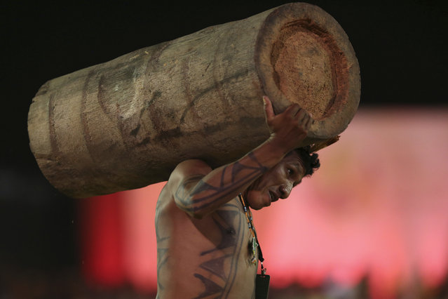 A Brazilian Xavante man carries a log in a race, during the first day of competition at the World Indigenous Games, in Palmas, Brazil, Saturday, October 24, 2015. Billed as the indigenous Olympics, the games are expected to attract nearly 2,000 athletes from dozens of Brazilian ethnicities, as well as from such far-flung nations as Ethiopia and New Zealand. (Photo by Eraldo Peres/AP Photo)