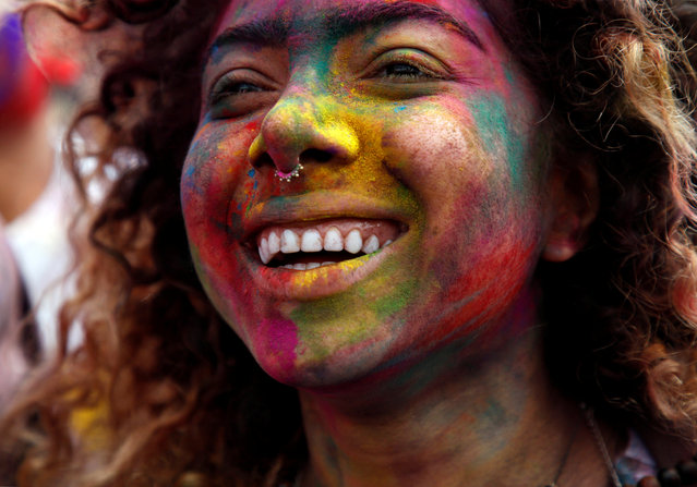 A woman, smeared with coloured powder, dance while celebrating Holi, the Festival of Colours, in Kathmandu, Nepal. (Photo by Navesh Chitrakar/Reuters)
