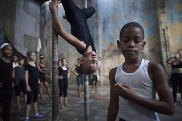 Children practise during a training session at a circus school in Havana, in this September 29, 2014 file photo. (Photo by Alexandre Meneghini/Reuters)