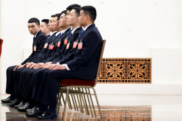 Security officers watch a live broadcast of the fourth plenary session of the National People's Congress (NPC) at the Great Hall of the People in Beijing, China, March 13, 2018. (Photo by Thomas Peter/Reuters)