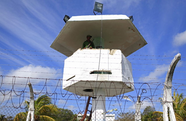 A military guard observes from a watch tower at the Combinado del Este prison during a media tour in Havana, Cuba, Tuesday, April 9, 2013.  Cuban authorities led foreign journalists through the maximum security prison, the largest in the Caribbean country that houses 3,000 prisoners. Cuba says they have 200 prisons across the country, including five that are maximum security. (Photo by Franklin Reyes/AP Photo)