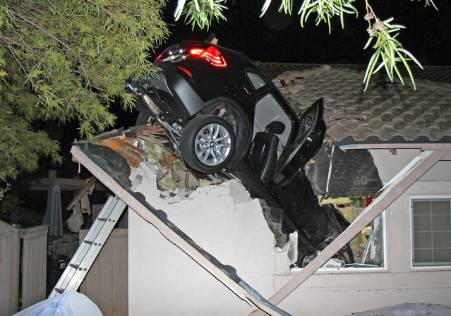 This photo provided by homeowner George Strother shows a sport utility vehicle that went airborne and sailed into the roof of his home in Escondido, Calif., around 12:30 a.m. Wednesday, December 11, 2014. Police said a BMW driver lost control during a turn, went off a road and plunged through the garage roof of a home that sits about 20 feet below the roadway. (Photo by George Strother/AP Photo)