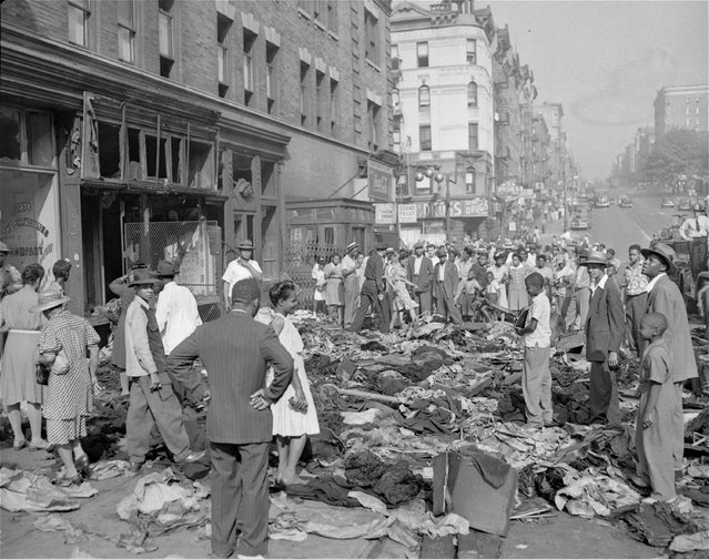 Bystanders gather to look over a pile of merchandise scattered over the sidewalk in front of a pawnshop at 145th Street and Eighth Avenue, August 2, 1943, an aftermath of Harlem disorders in New York City. (Photo by AP Photo)
