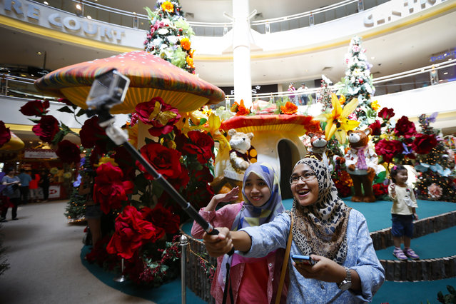 Muslim women pose for selfie in front of Christmas decorations at a shopping mall in Malaysia Wednesday, December 10, 2014. Shopping malls in Muslim-dominated Malaysia have been decorated with Christmas trees, lights and Santa Claus to attract year-end shoppers. (Photo by Vincent Thian/AP Photo)