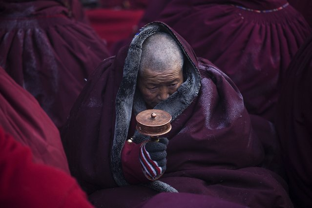 A Tibetan Buddhist nun spins a prayer wheel in sub zero temperatures at a Buddhist laymen lodge where thousands of people gather for daily chanting session during the Utmost Bliss Dharma Assembly, the last of the four Dharma assemblies at Larung Wuming Buddhist Institute in remote Sertar county, Garze Tibetan Autonomous Prefecture, Sichuan province, China November 1, 2015. (Photo by Damir Sagolj/Reuters)