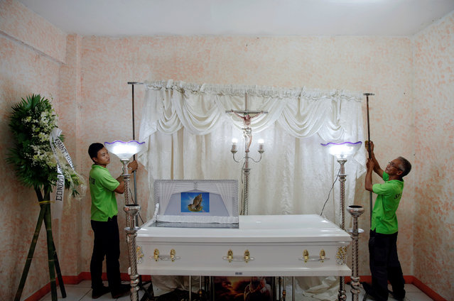 Funeral parlour workers arrange the curtain behind a coffin with a man whose body was found earlier this week with a placard accusing him of being a drug pusher, in a community centre where relatives and friends gathered to mourn his death in Manila, Philippines October 8, 2016. (Photo by Damir Sagolj/Reuters)