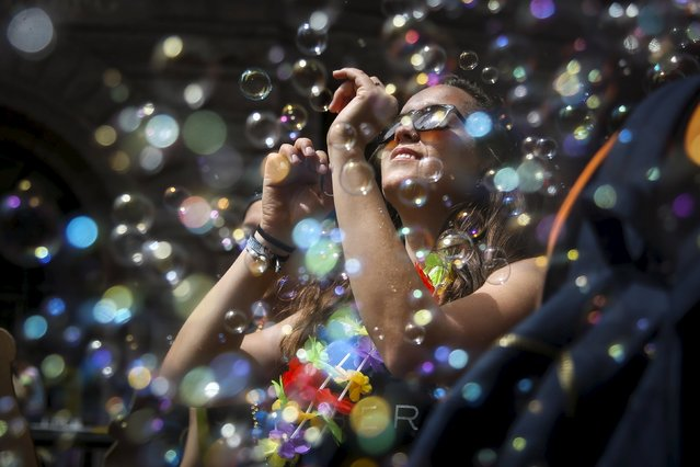 A woman dances in a cloud of bubbles while marching in a gay pride parade in San Francisco, California June 28, 2015. (Photo by Elijah Nouvelage/Reuters)
