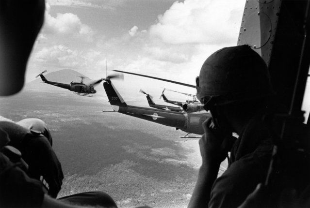 A crewman in a US helicopter watches a group of escorting Bell Huey helicopters during an operation in  the Vietnam War, 1968. (Photo by Terry Fincher/Daily Express/Hulton Archive/Getty Images)