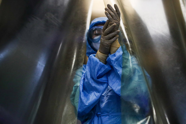 """A medical staff member takes off a protective suit after a shift in the """"red zone"""" at Moscow's City Hospital No 15 (Filatov Hospital) treating COVID-19 patients in Moscow, Russia on October 28, 2020. (Photo by Sergei Bobylev/TASS)"""