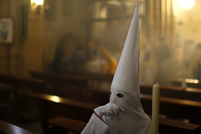 """A hooded penitent from the """"El Resucitado"""" brotherhood takes part in a Holy Week procession in Cordoba, southern Spain, Sunday, April 1, 2018. Hundreds of processions take place throughout Spain during the Easter Holy Week. (Photo by Manu Fernandez/AP Photo)"""