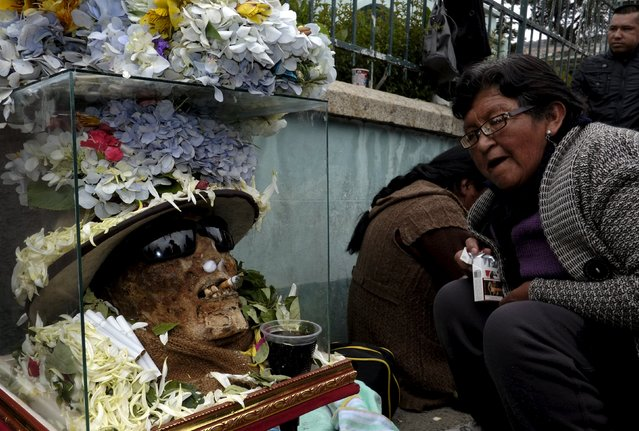 """A devotee sits near skulls placed on the floor during a ceremony held for the """"Dia de las natitas"""" (Day of the Skull) celebrations at the General Cemetery of La Paz, November 8, 2015. (Photo by David Mercado/Reuters)"""