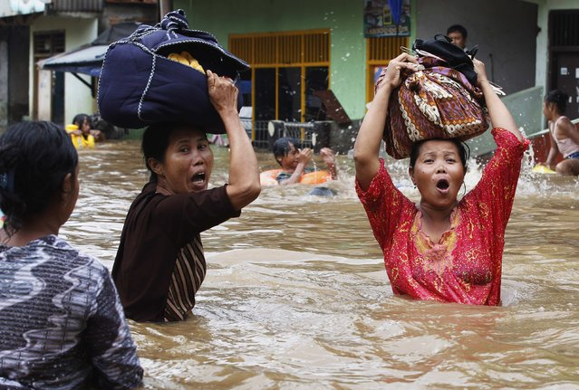 Women react as they flee from their flooded area in Jakarta in this January 17, 2013 file photo. (Photo by Enny Nuraheni/Reuters)