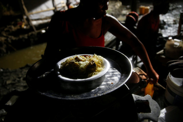A woman serves a plate of spaghetti to a client on the street after Hurricane Matthew hit Jeremie, Haiti, October 14, 2016. (Photo by Carlos Garcia Rawlins/Reuters)