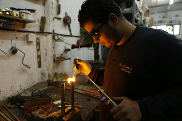 A worker welds at a shisha manufacturing factory in Baghdad December 17, 2014. (Photo by Thaier Al-Sudani/Reuters)