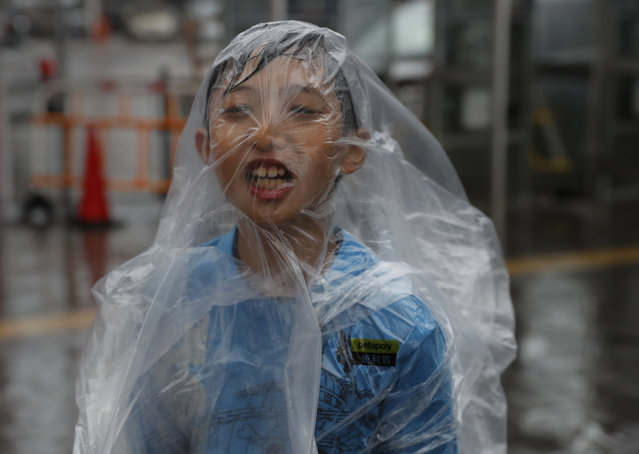 A boy braves the wind on the waterfront of Victoria Habour as Typhoon Haima approaches Hong Kong, Friday, October 21, 2016. (Photo by Vincent Yu/AP Photo)