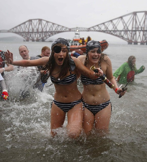 Swimmers in fancy dress splash as they participate in the New Year's Day Loony Dook swim at South Queensferry, Scotland January 1, 2015. (Photo by Russell Cheyne/Reuters)