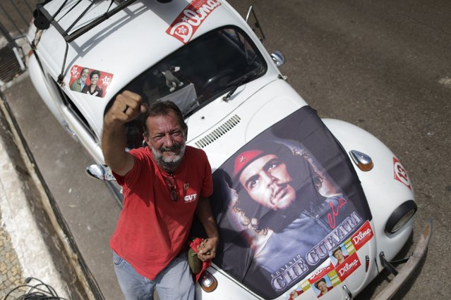 Carlos Magno, 54, raises his fist after travelling 2,500 km from Belem in a Volkswagen Fusca to attend the inauguration of President Dilma Rousseff, in front of the Planalto Palace in Brasilia December 31, 2014. Rousseff's inauguration is scheduled to take place on January 1, 2015. (Photo by Ueslei Marcelino/Reuters)