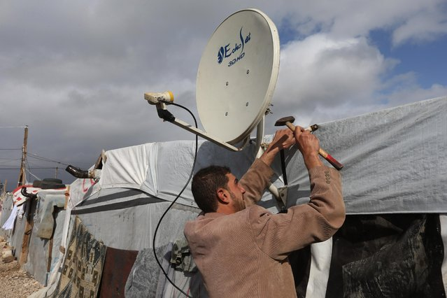 A Syrian man fixes a TV satellite outside of his tent at a refugee camp in Deir Zannoun village, Bekaa valley, Lebanon, Tuesday, January 6, 2015. (Photo by Hussein Malla/AP Photo)