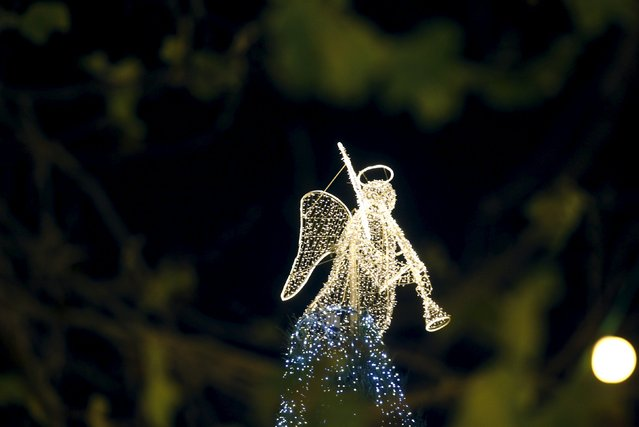 An illuminated angel is seen through a tree on the opening day of the Christmas Market in Dortmund, Germany, November 23, 2015. (Photo by Ina Fassbender/Reuters)