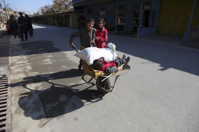 An Afghan boy and his sister use a wheelbarrow to move their brother in Istalef district of Kabul, Afghanistan, Saturday, November 21, 2020. (Photo by Rahmat Gul/AP Photo)