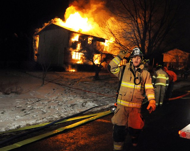 A firefighter gestures to move back during a three-alarm blaze that destroyed a home on Grandview Drive in Scott Township, Pennsylvania on Wednesday, January 7, 2015. The blaze lasted into early Thursday morning in subzero temperatures. (Photo by Butch Comegys/AP Photo/The Scranton Times-Tribune)