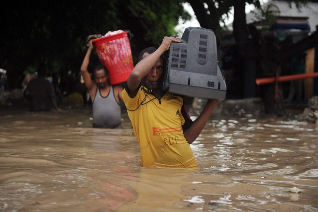 A man carries a television through waist-deep flood water in Mogadishu on May 20, 2018 after homes were inundated in Somalia's capital following heavy overnight rainfall. (Photo by Mohamed Abdiwahab/AFP Photo)