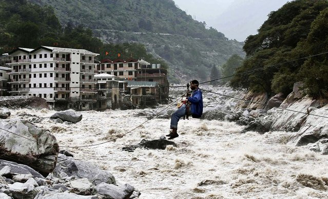 A man crosses over a swollen river with the help of a rope in Govindghat, India, on June 23, 2013. Bad weather hampered efforts Sunday to evacuate thousands of people stranded in the northern India state of Uttarakhand, where at least 1,000 people have died in monsoon flooding and landslides, army officials said. (Photo by Rafiq Maqbool/Associated Press)