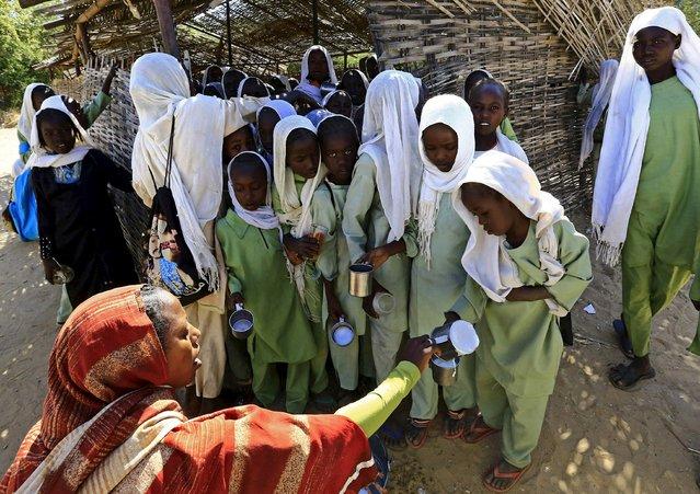 An internally displaced teacher distributes milk to schoolgirls at the El Geneina camp in West Darfur, Sudan, November 24, 2015. (Photo by Mohamed Nureldin Abdallah/Reuters)