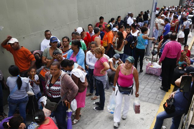 People queue to buy goods in a Mega-Mercal, a subsidized state-run street market, in Caracas January 24, 2015. (Photo by Carlos Garcia Rawlins/Reuters)