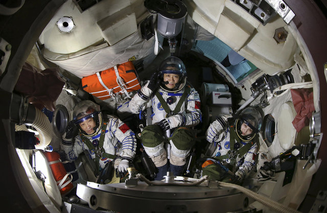 Chinese astronauts (from left) Zhang Xiaoguang, Nie Haisheng and Wang Yaping salute in a re-entry capsule during a training at Beijing Aerospace City in Beijing, on April 29, 2013. (Photo by Reuters/Stringer via The Atlantic)