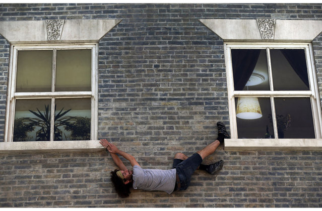 A visitor enjoys an art installation by Argentine artist Leandro Erlich in east London, Tuesday, July 9, 2013. Internationally known for his three-dimensional visual illusions, Erlich has been commissioned to create a new installation in Dalston area of the capital. Resembling a theatre set, the detailed facade of a Victorian terraced house, recalling those that once stood on the street, lies horizontally on the ground with mirrors positioned overhead. The reflections of visitors give the impression they are standing on, suspended from, or scaling the building. (Photo by Lefteris Pitarakis/AP Photo)