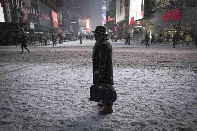 A man stands in falling snow on West 42nd street in Times Square in New York, January 26, 2015. (Photo by Mike Segar/Reuters)