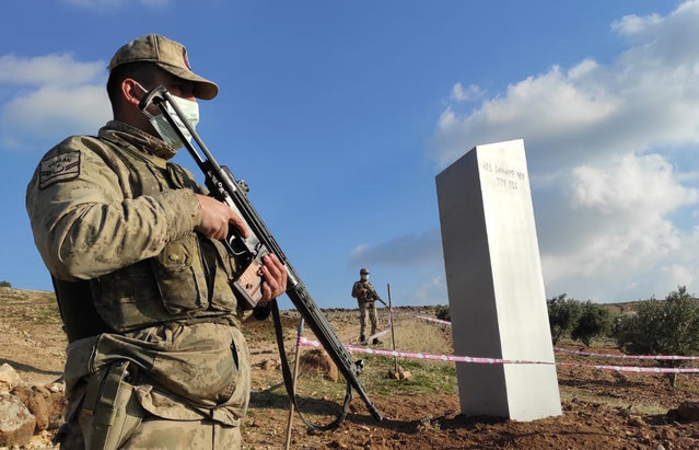 """Turkish police officers guard a monolith, found on an open field near Sanliurfa, southeastern Turkey, Sunday, February 7, 2021. The metal block was found by a farmer Friday in Sanliurfa province with old Turkic script that reads """"Look at the sky, see the moon."""" The monolith, 3 meters high (about 10 feet), was discovered near UNESCO World Heritage site Gobeklitepe with its megalithic structures dating back to 10th millennium B.C. Turkish media reported Sunday that gendarmes were looking through CCTV footage and investigating vehicles that may have transported the monolith. Other mysterious monoliths have popped up and some have disappeared in numerous countries since 2020. (Photo by Bekir Seyhanli/IHA via AP Photo)"""