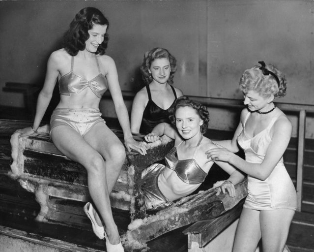 Models sitting on a coffin filled with ice at the Festival Gardens, 1951. They each took turns to lie in the coffin, dressed only in swimming costumes. (Photo by Fox Photos/Getty Images)