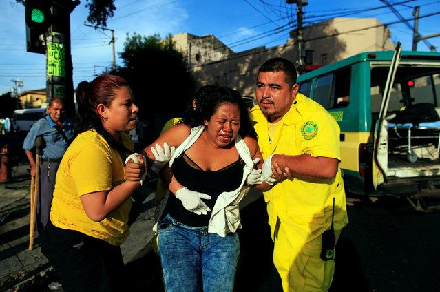 Rescuers Maria Martinez (L) and Renato Landaverde help a woman who was run over by a bus in San Salvador, El Salvador July 17, 2016. (Photo by Jose Cabezas/Reuters)