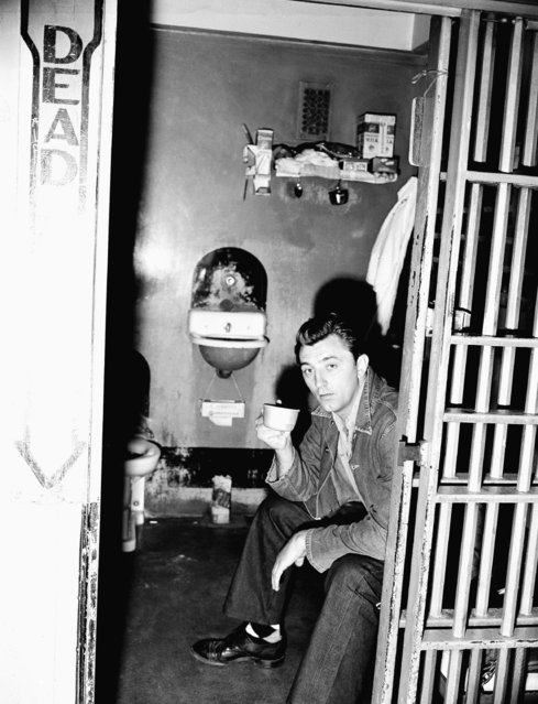 Movie star Robert Mitchum sips a cup of soup in his cell in the Los Angeles County jail as he begins a 60 day sentence for conspiracy to possess marijuana. A faded blue denim shirt replaced the natty business suit he wore to court on February 10, 1949, but he still had on his own argyle socks. (Photo by Harold Filan/AP Photo)
