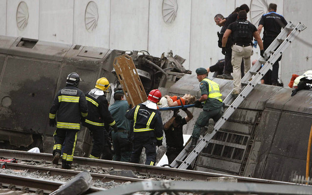 A woman is evacuated by emergency personnel at the scene of a train derailment in Santiago de Compostela, Spain, on Wednesday, July 24, 2013. A train derailed in northwestern Spain on Wednesday night, toppling passenger cars on their sides and leaving at least one torn open as smoke rose into the air. Dozens were feared dead, with possibly even more injured. (Photo by Antonio Hernandez/AP Photo/El correo Gallego)