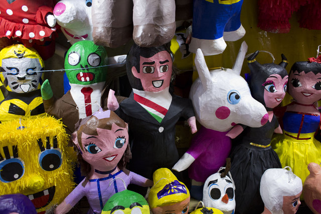 In this January 23, 2015 photo, a piñata designed to resemble Mexican President Enrique Pena Nieto is displayed with other piñatas representing popular children's characters, at a La Merced market stall run by Gerardo Moreno Alejo and his wife Edith. Piñata vendors keep the craftsmen apprised of the market. (Photo by Rebecca Blackwell/AP Photo)