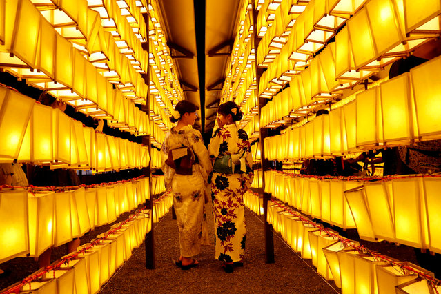 Women in yukatas, or casual summer kimonos, pose to take their photos between paper lanterns during the annual Mitama Festival at the Yasukuni Shrine, where more than 2.4 million war dead are enshrined, in Tokyo, Japan July 13, 2018. (Photo by Kim Kyung-Hoon/Reuters)