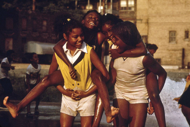 Youngsters cool off with fire hydrant water in the Woodlawn Community, June 1973. (Photo by John H. White/NARA via The Atlantic)