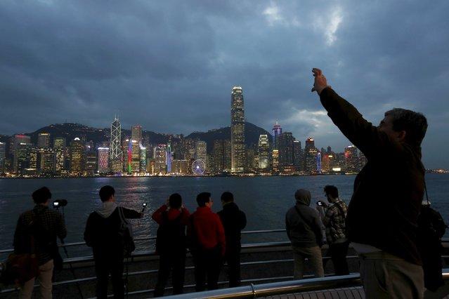 Visitors take photos on the waterfront of Kowloon peninsula facing Victoria Harbour and Hong Kong island in Hong Kong, China January 12, 2016. (Photo by Bobby Yip/Reuters)