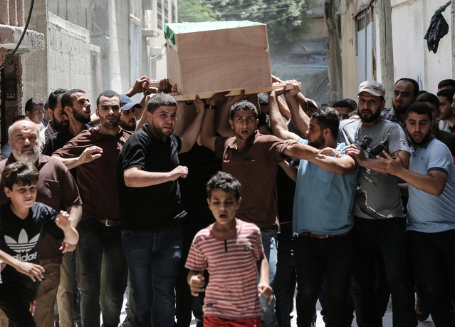 Palestinian mourners carry the body of Obada Farwana, during his funeral in Gaza City on July 26, 2018. The military wing of Gaza's rulers Hamas vowed revenge after Israeli strikes killed three militants, including Farawna, in the latest flare-up of violence. (Photo by Mahmud Hams/AFP Photo)