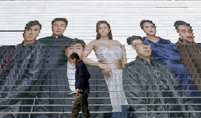 A man wearing a face mask as a precaution against the coronavirus, walks past in front of an advertisement of an opera performance outside of a theater in Seoul, South Korea, Wednesday, March 3, 2021. (Photo by Lee Jin-man/AP Photo)