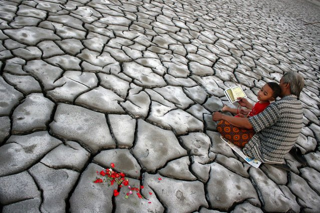 Indonesian man with his son pray after offering flowers on the dried volcanic mud for family members who died during a volcano eruption in Sidoarjo in eastern Java, on August 9, 2013. The May 2006 disaster killed 12 people, displaced nearly 50,000 and buried 13 villages. (Photo by AFP Photo)