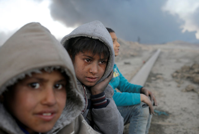 Boys sit in front of oilfields burned by Islamic State fighters in Qayyara, south of Mosul, Iraq November 23, 2016. (Photo by Goran Tomasevic/Reuters)