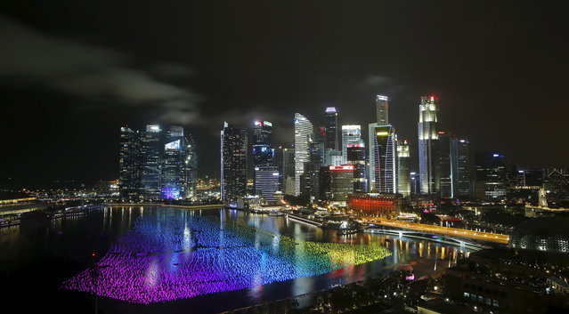 """Tens of thousands of floating """"wishing spheres"""" carrying people's New Year wishes line the Marina Bay against the skyline of Singapore December 31, 2015. (Photo by Edgar Su/Reuters)"""