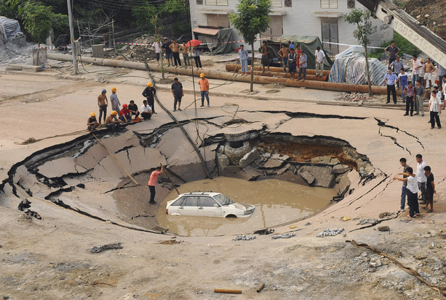 A stranded car is hoisted from a collapsed road surface in Guangzhou, Guangdong province, September 7, 2008. The road collapsed on Sunday afternoon and trapped the car in a hole, which measured 5 meters (16.4 feet) in depth and 15 meters (49.2 feet) in diameter, local media reported. Further investigation is underway. Picture taken September 7, 2008. (Photo by Reuters/China Daily)